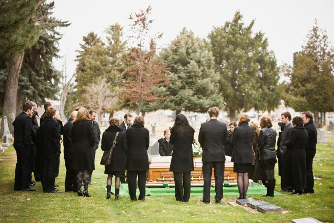 People standing at funeral in cemetery