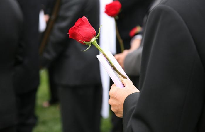 Man holding a funeral program