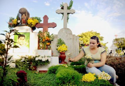 A Nicaraguan woman decorates a grave