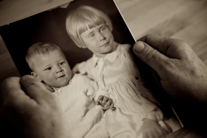 Holding a photo of siblings