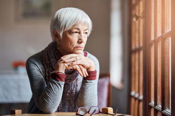 Senior woman looking pensively out window