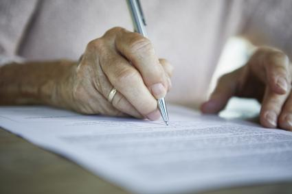 Senior woman signing a document
