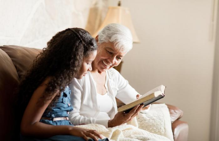 Woman reading bible with granddaughter