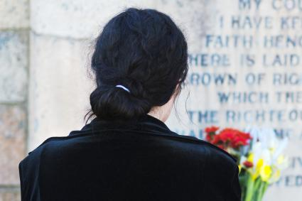 Rear view of woman by gravestone with flowers