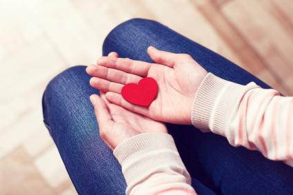 Red paper heart in female hands