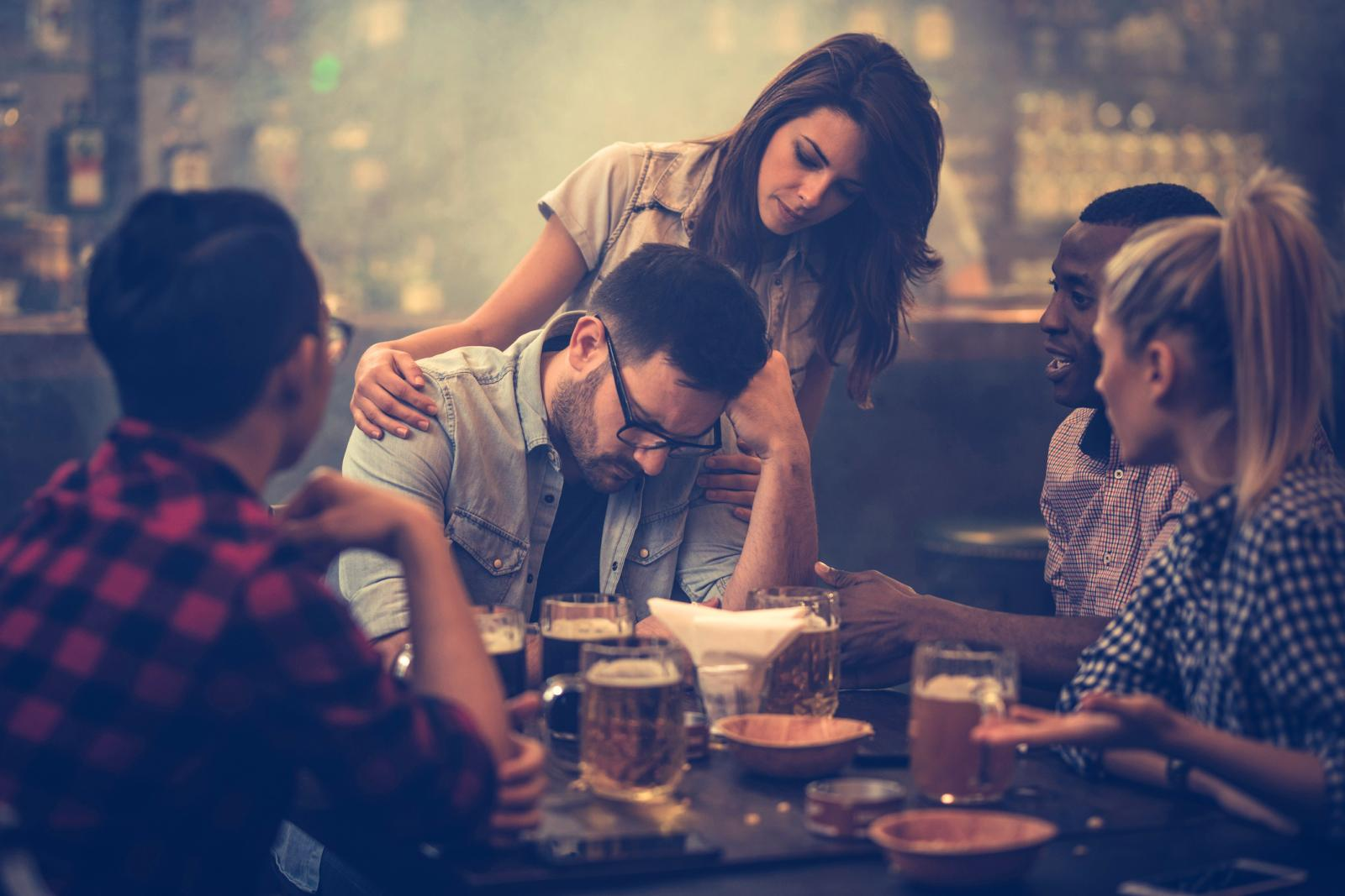 Group of friends consoling their friend who is sitting displeased in a bar