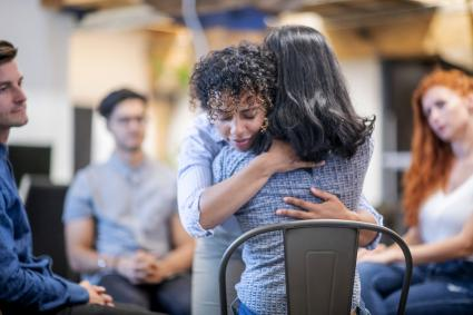 Two women hugging during a support group meeting