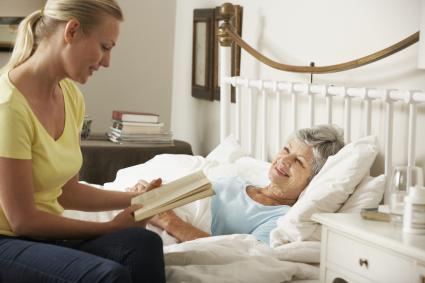 Woman reading to hospice patient
