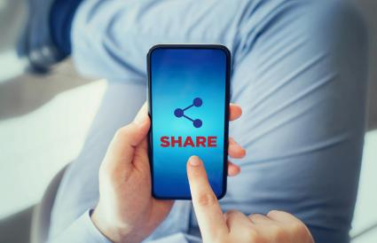 man touching share icon on smart phone
