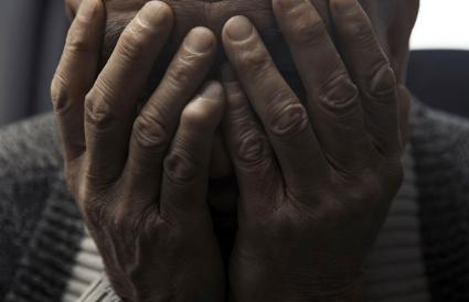 man covers his face with hands