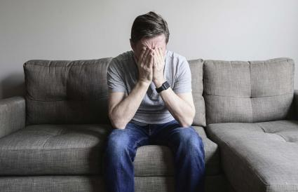 Depressed mature man sitting on couch