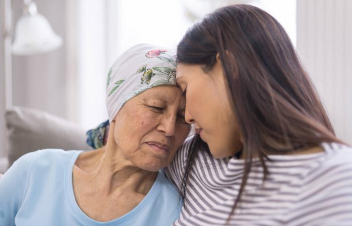elderly woman embracing her daughter
