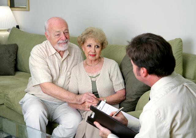 A senior couple talking with a funeral director