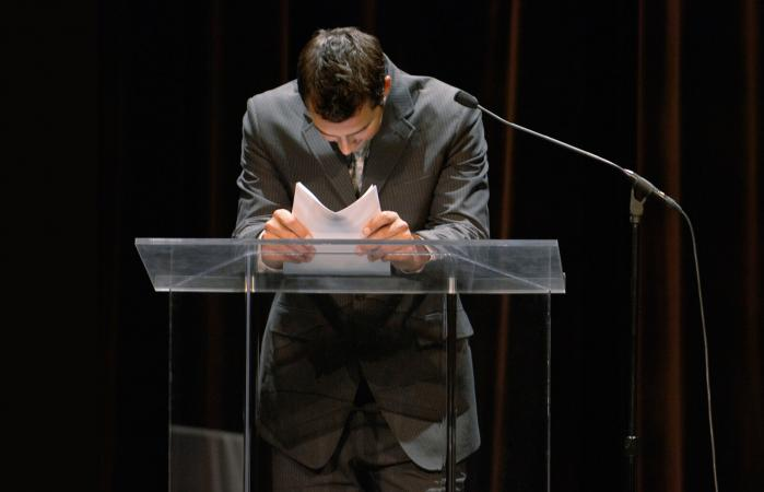 man leaning on podium