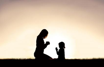 Mother praying with her young child