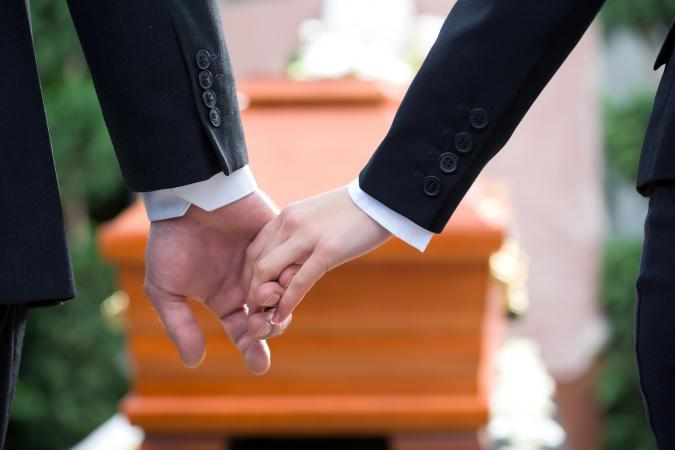 Two people holding hands at a funeral