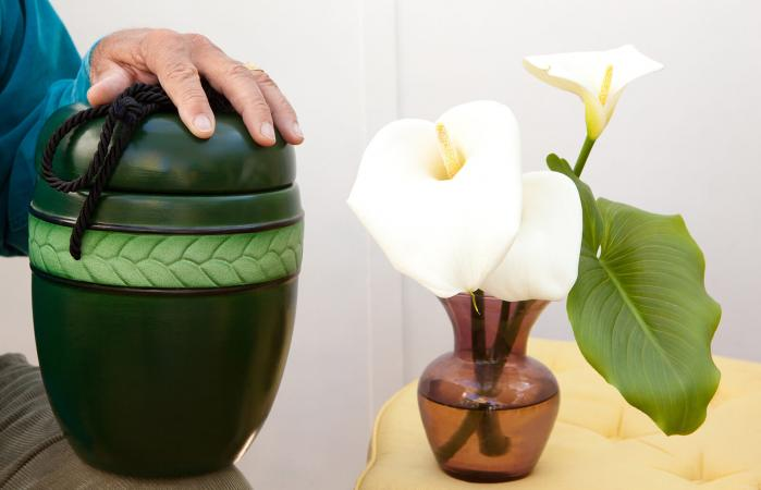 Cremation urn and flowers in a vase
