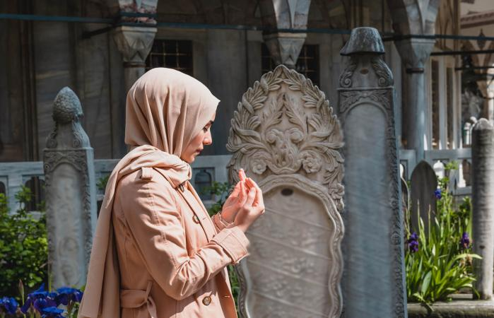 Muslim woman in hijab prays