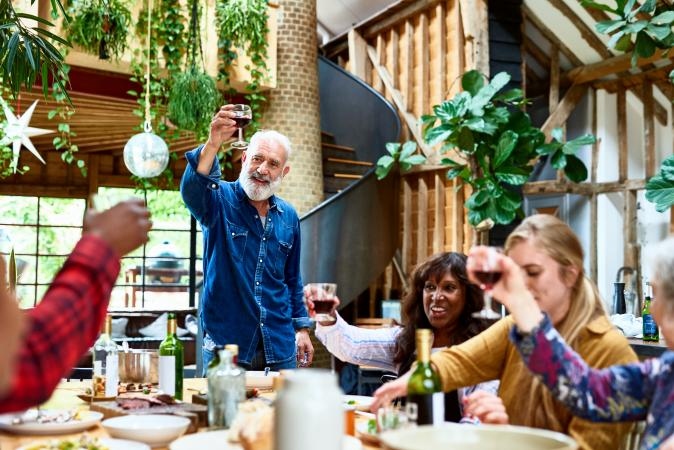 Cheerful man raising wine glass in a toast with friends