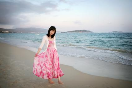 Girl wearing pink and white dress walking on beaching