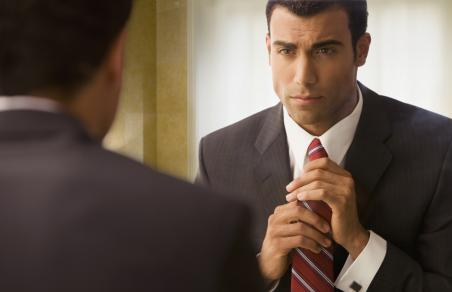 Man in business suit adjusting tie in mirror