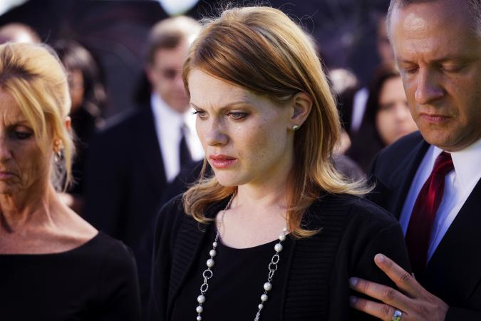 A grieving widow standing in a funeral