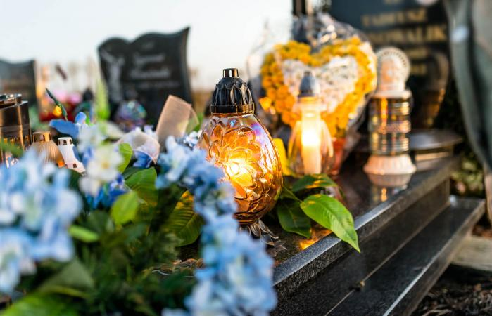 flowers and candlesticks on tombstone