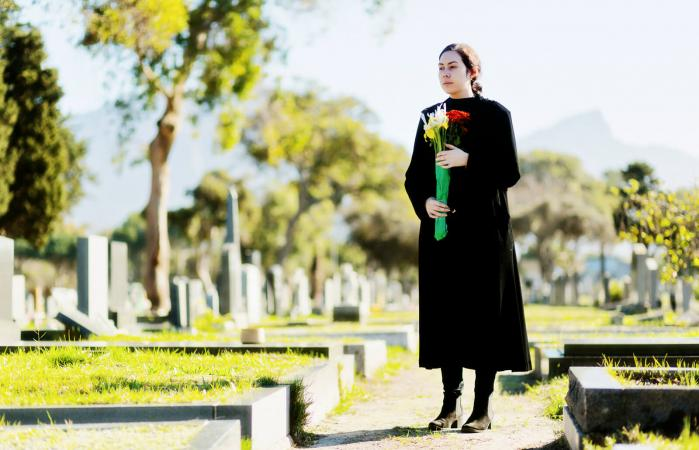 woman carrying flowers on cemetery path