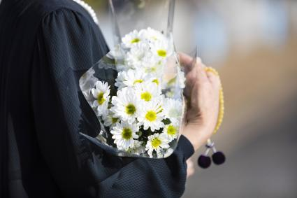 Woman holds old white chrysanthemum and beads in her hands