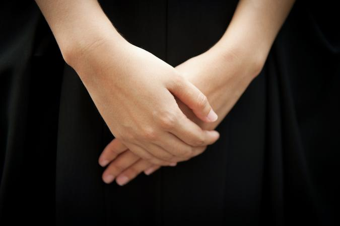 Woman wearing black respectfully folding her hands