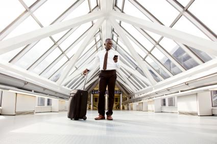 Man wearing formal wear standing in a airport with luggage