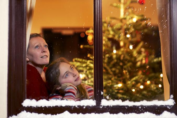 Girl and mother gazing out of window at christmas