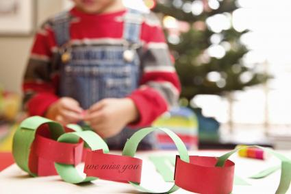 Boy making paper garland for Christmas