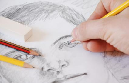 A hand is drawing a portrait