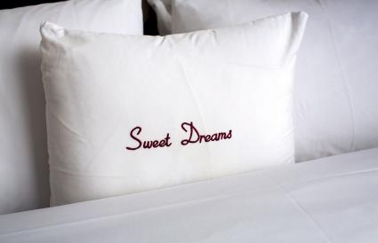Bed with Sweet Dreams embroidered white pillow