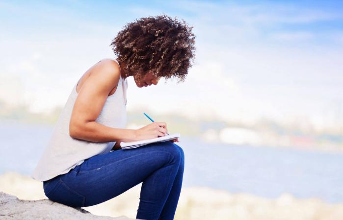 Woman writing in a notebook outdoors