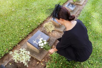 Woman Holding Flowers Next to a Headstone