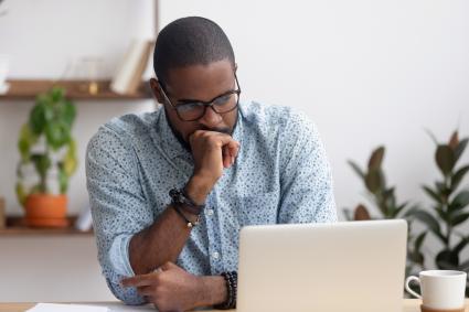 Man reading sad news on computer