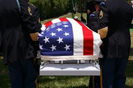 Militaries holding a coffin covered with the American flag