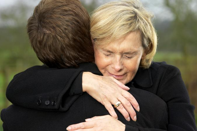 Crying Woman Hugging a Man Before a Funeral
