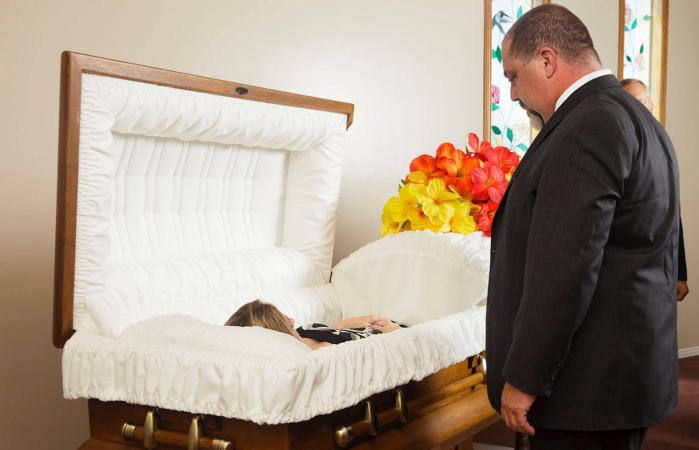 man at funeral viewing