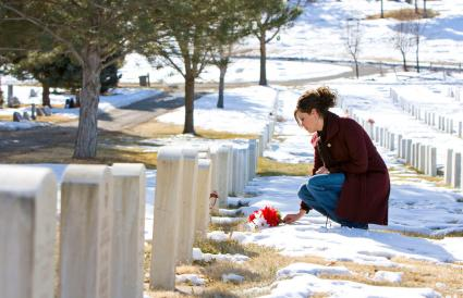 Mourning young woman at graveside