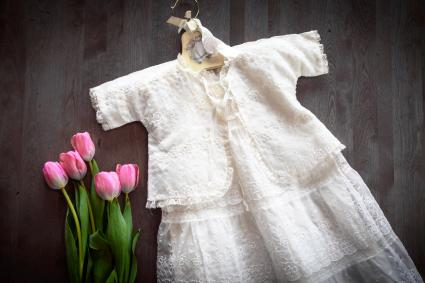 White baby gown and tulips on wood background