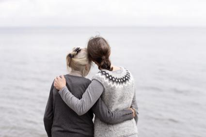 Two generations women embracing, looking at sea