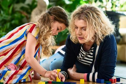 Young girl concentrating on building blocks with her mother and talking