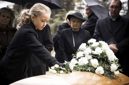 Little girl laying flowers on the coffin