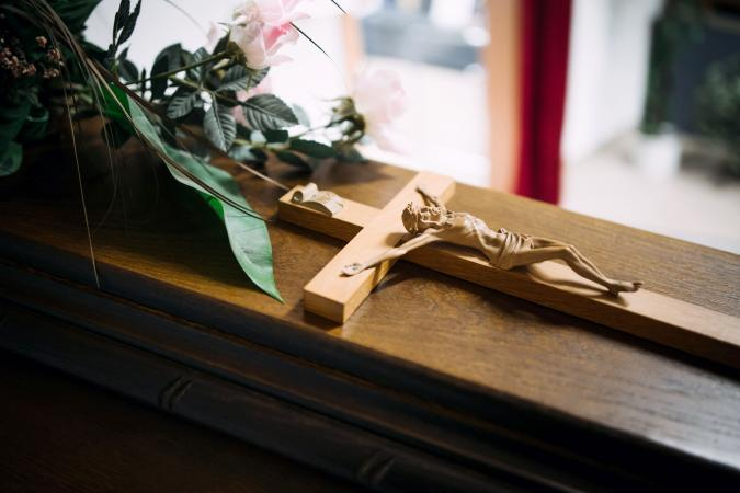 Cross on a wooden casket at a funeral
