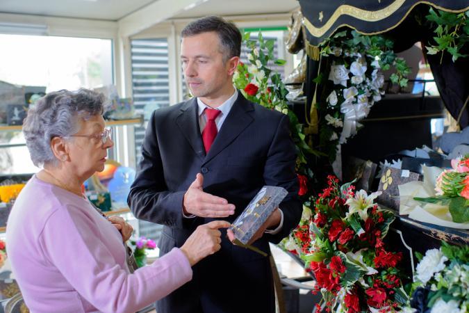 Funeral director showing woman memorial plaque