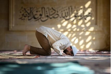 Muslim man is praying in mosque