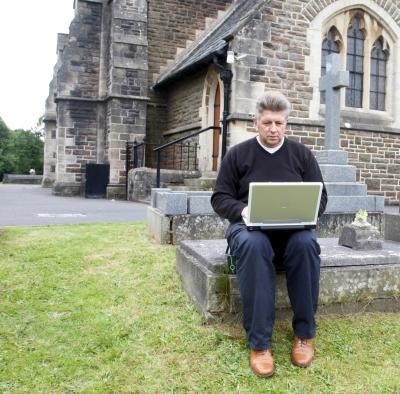 Man sitting in a church cemetery while using a laptop